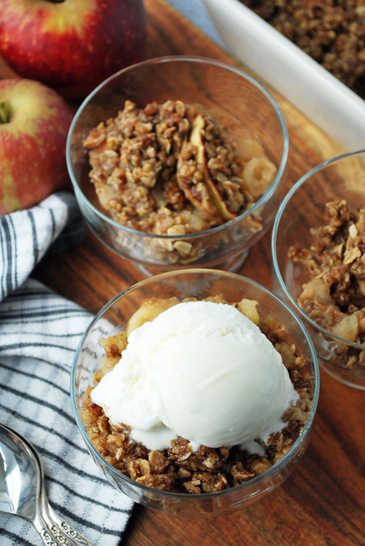 overhead photo of 3 dishes of apple crisp and pan of crisp with whole apples in the background