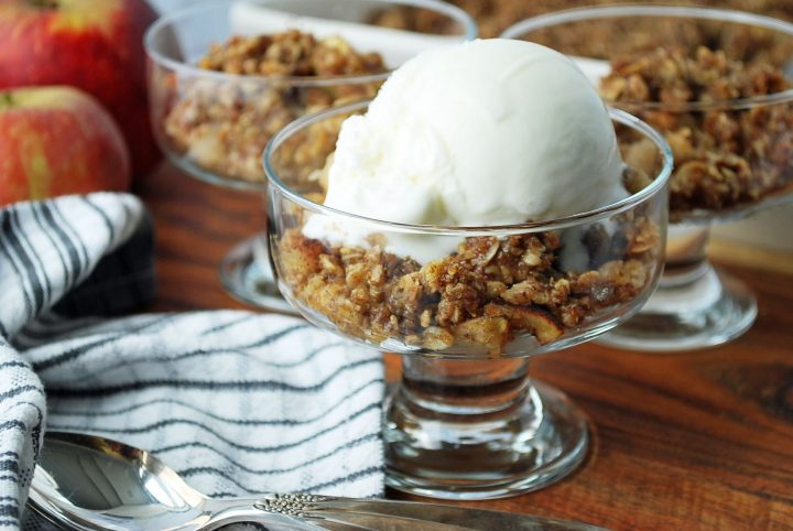 dessert dishes of apple crisp with napkin and apples in the background