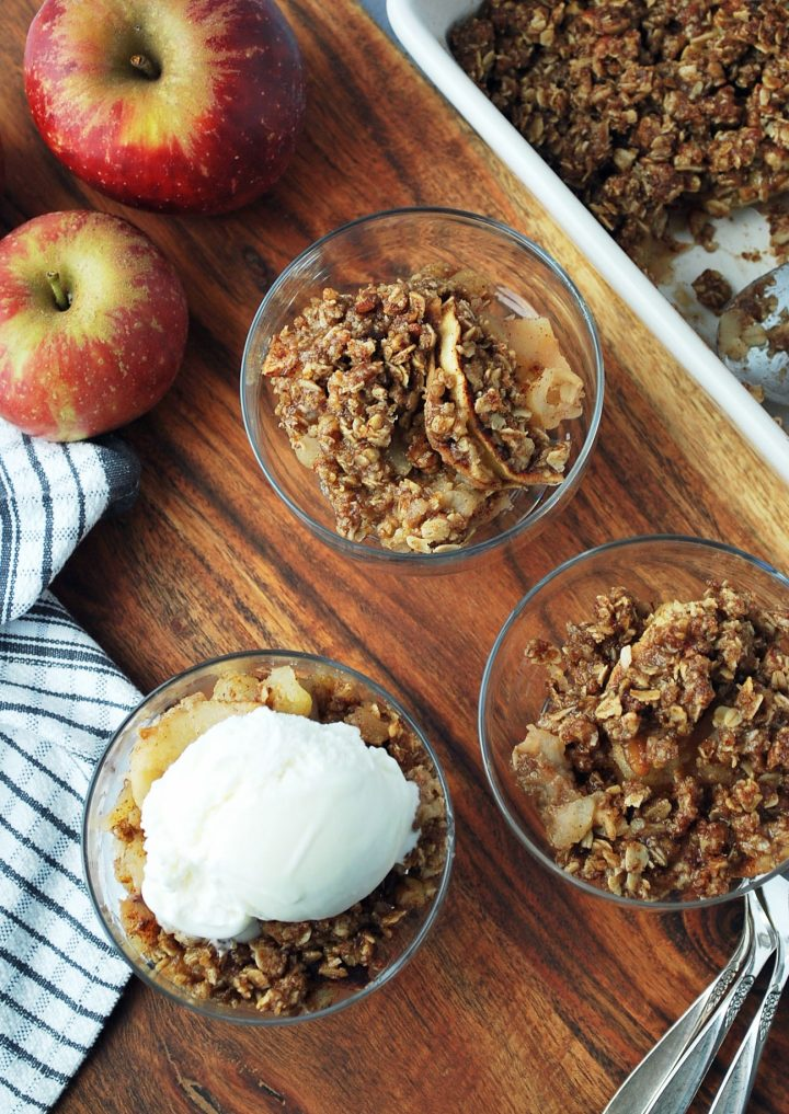 wooden tray with parfait dishes of apple crisp and an apple in the background