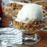 close up photo of parfait dish with apple crisp and a scoop of vanilla ice cream