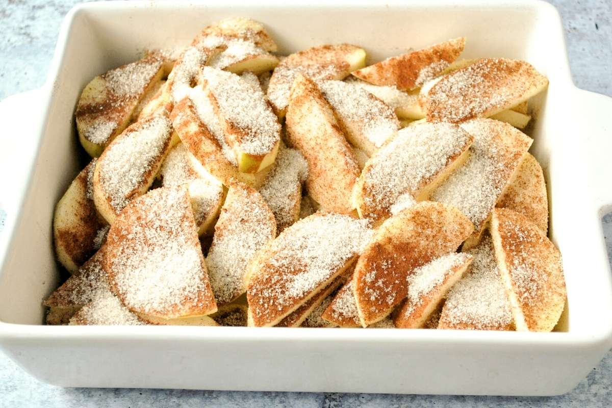 apples in baking dish sliced and sprinkled with cinnamon and sugar