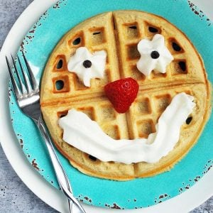 A waffle on a plate decorated as a smiley face with whipped cream, strawberries, and chocolate chips