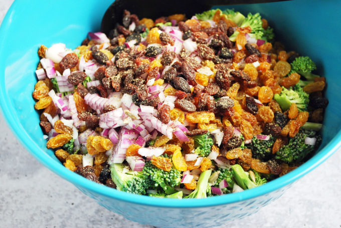 Broccoli salad ingredients in a blue bowl
