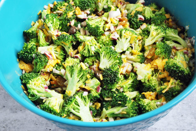 Broccoli salad ingredients tossed with dressing in a bowl