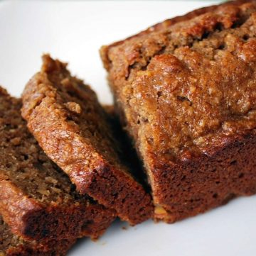a small loaf of banana bread sliced on a white plate