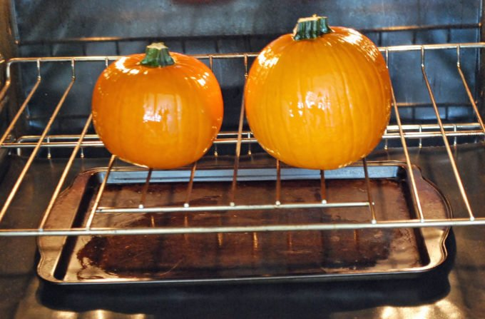 Whole pumpkins roasting in the oven for homemade pumpkin puree