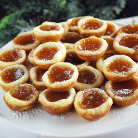 Apricot Tarts on a white platter with greenery in the background