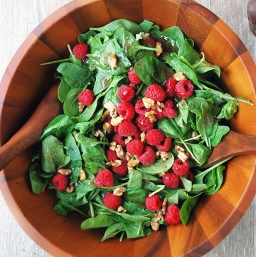 bowl of raspberry spinach salad with walnuts