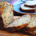 Sliced date nut quick bread on a cutting board with a plate of buttered bread in the background