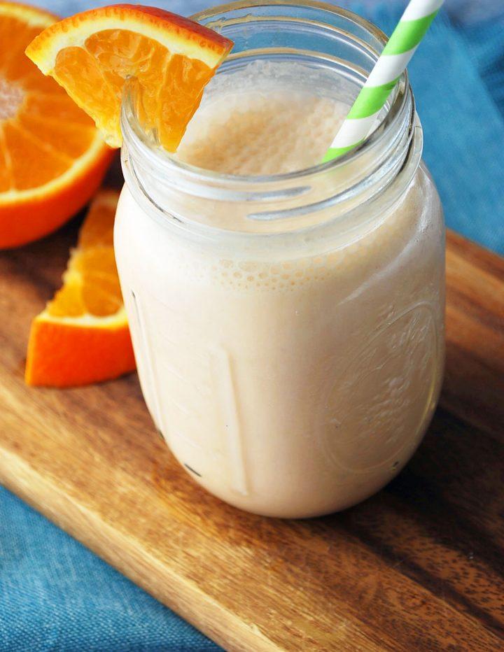 orange creamsicle shake with green straw and orange wedge