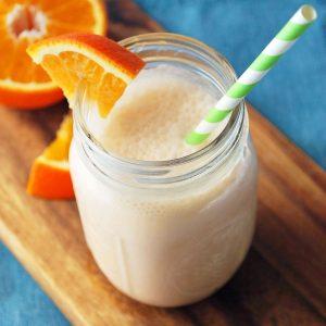 orange creamsicle shake in a mason jar on top of a wood cutting board with orange slices