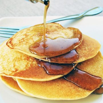 plate of buttermilk pancakes with syrup poured on top