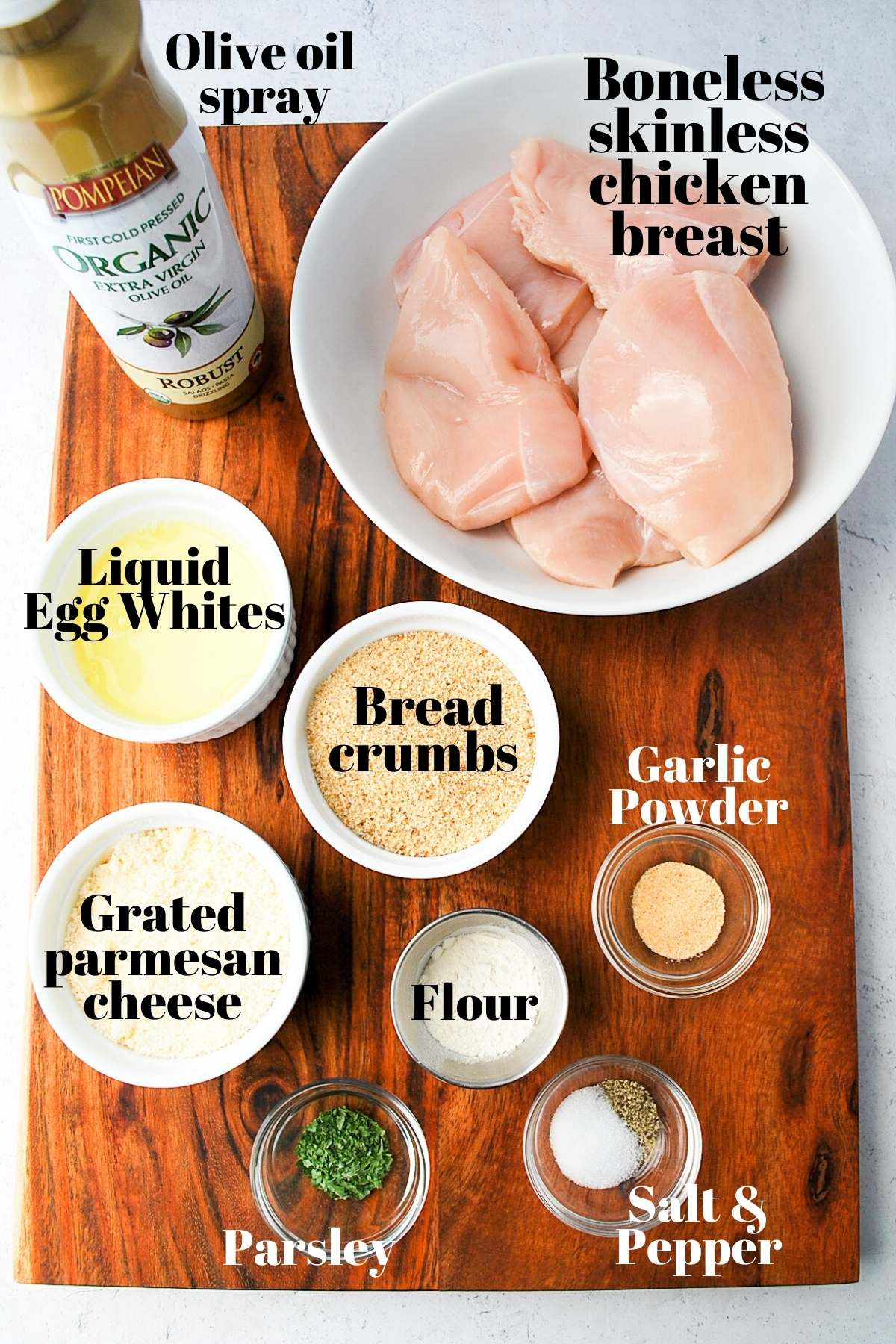 ingredients for air fryer parmesan crusted chicken on a wooden cutting board