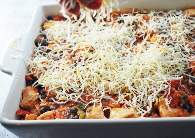 Topping this easy Mexican chicken casserole with grated cheese