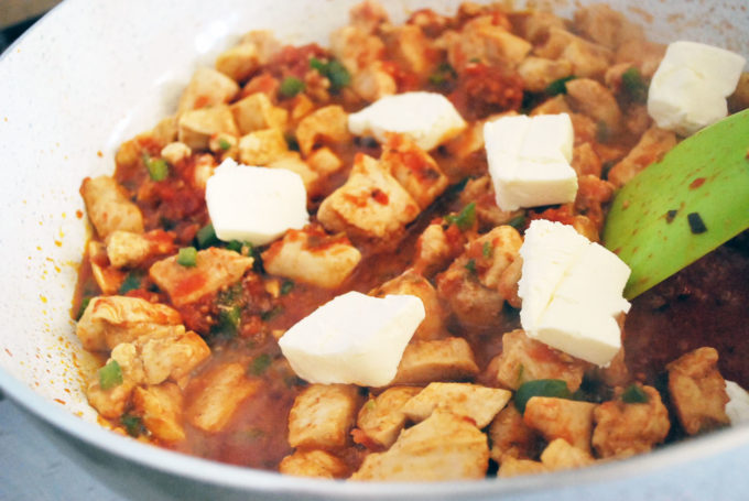 Cream cheese added to chicken mixture for easy Mexican casserole