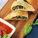 spinach calzone on a cutting board with marinara sauce