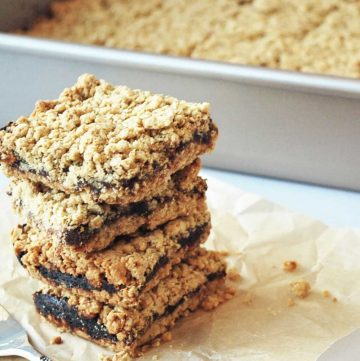 four oatmeal date bars stacked on parchment paper with the pan of sliced bars in the background