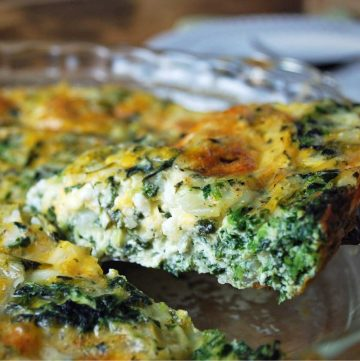close up of a slice of spinach quiche raised from the dish with a spatula
