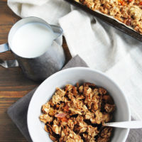 homemade granola in a cereal bowl and on a baking sheet and a small pitcher of milk