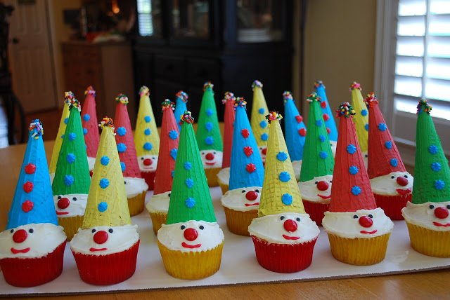 Clown cupcakes on a tray with assorted colored hats