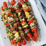 overhead photo of chicken kabobs on a white platter with a napkin underneath