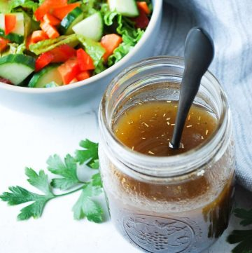 maple balsamic vinaigrette dressing in a jar with a spoon and a salad in the background