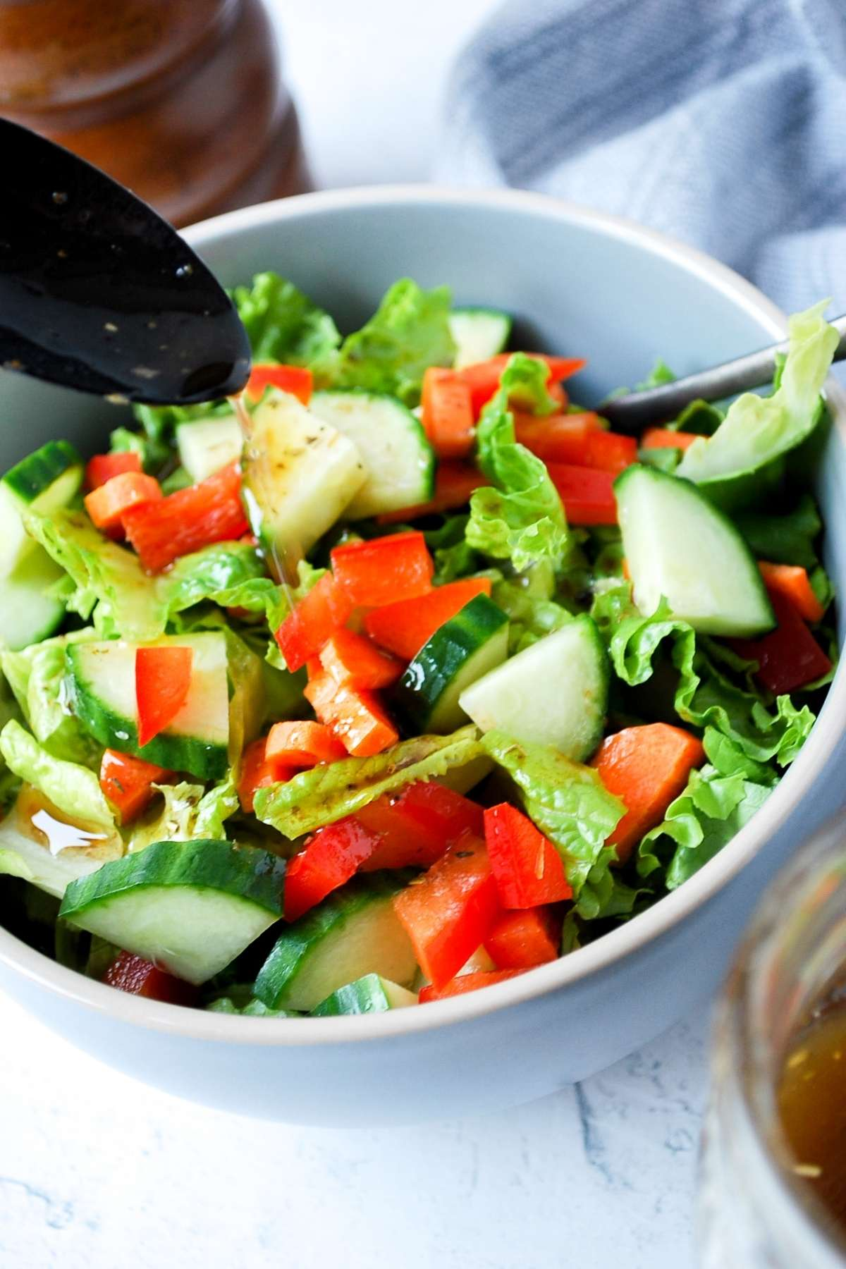 a spoon drizzling dressing on a garden salad