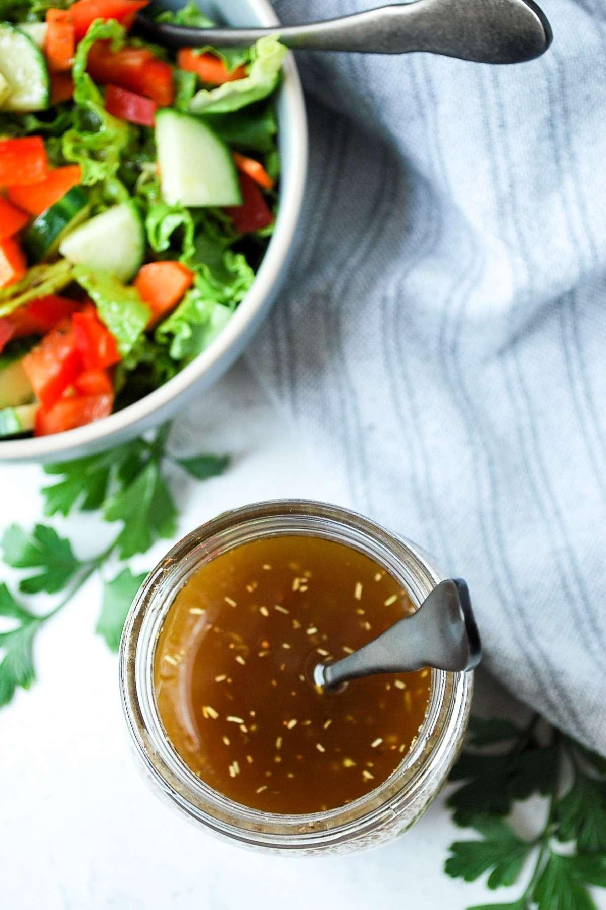 overhead shot of a jar of maple balsamic vinaigrette next to a bowl of garden salad
