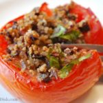 A close-up of a stuffed half tomato being sliced with a fork