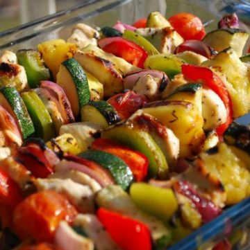 grilled chicken kabobs in a glass baking dish