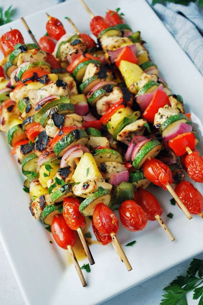 chicken and vegetable kabobs on a white platter sprinkled with parsley