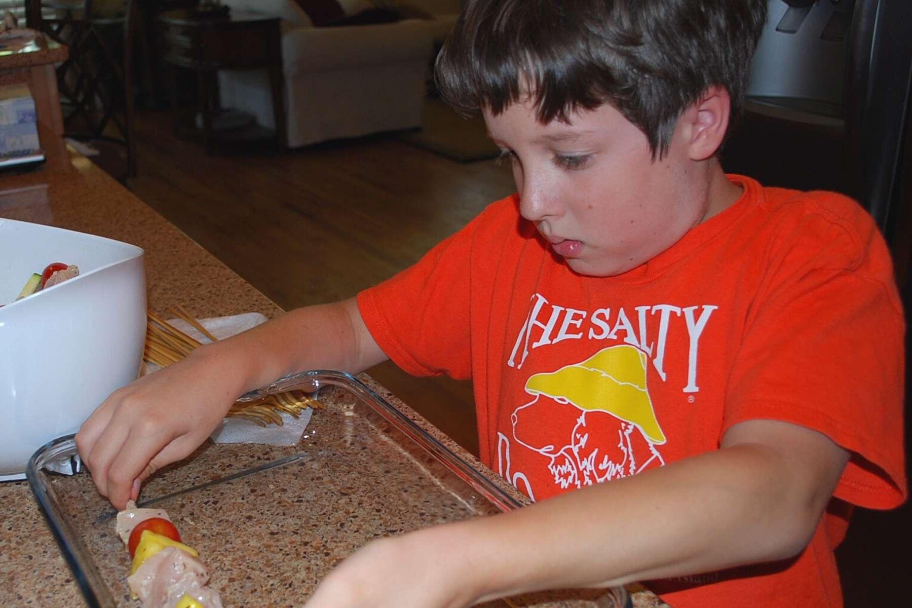 little boy assembling kabobs