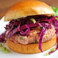 These grilled Asian-style pork burgers are juicy and flavorful made with ground pork, garlic, ginger, sesame oil, green onions, and spices topped with a simple red cabbage slaw.