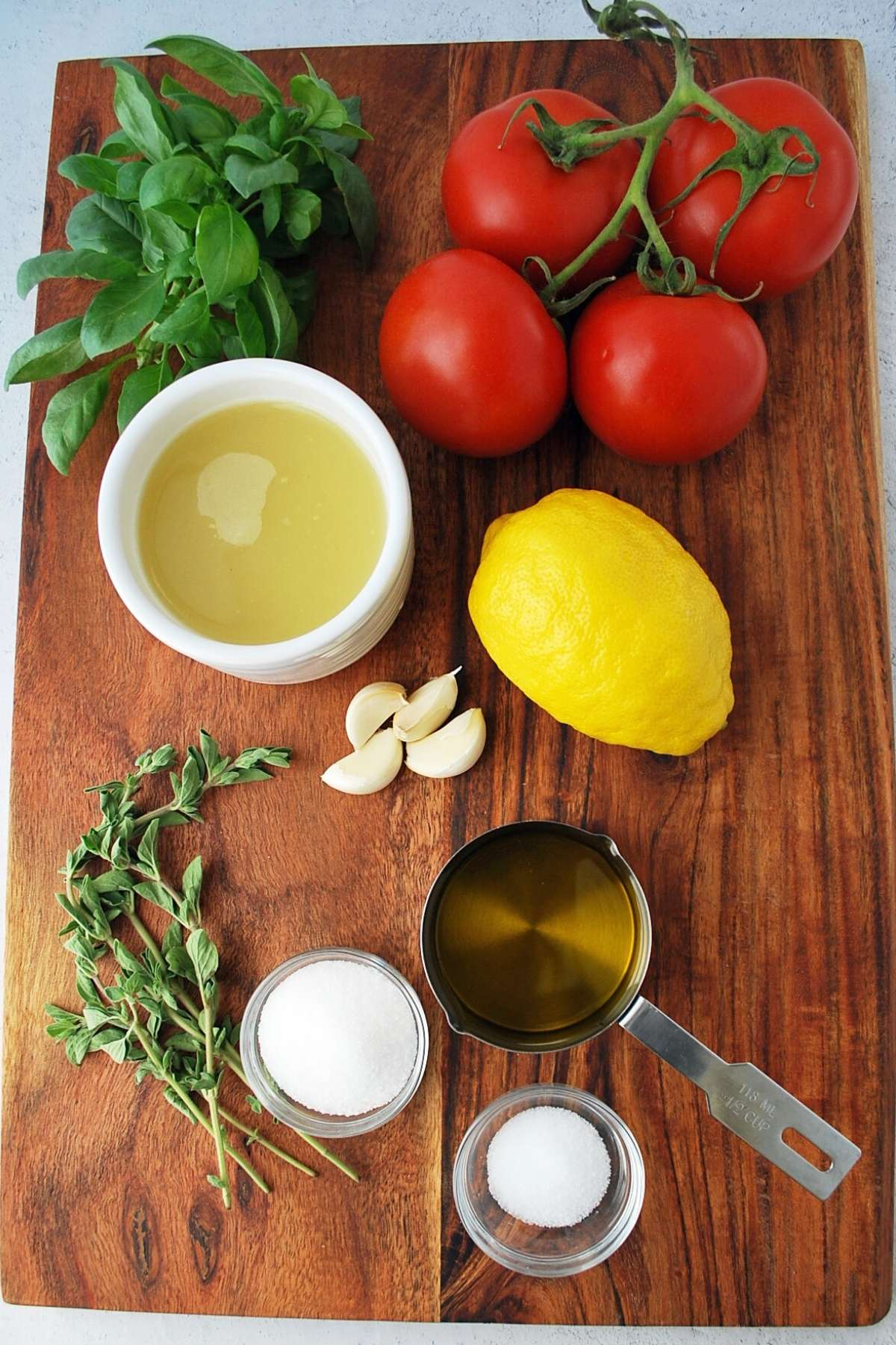 ingredients for tomato basil pasta sauce on a cutting board