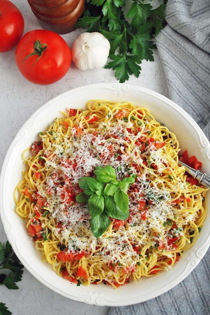 overhead photo of pasta tossed with tomato basil sauce and cheese with tomatoes, garlic, and herbs in the background