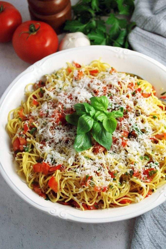 large bowl of pasta tossed with fresh tomato basil sauce and garnished with basil and cheese