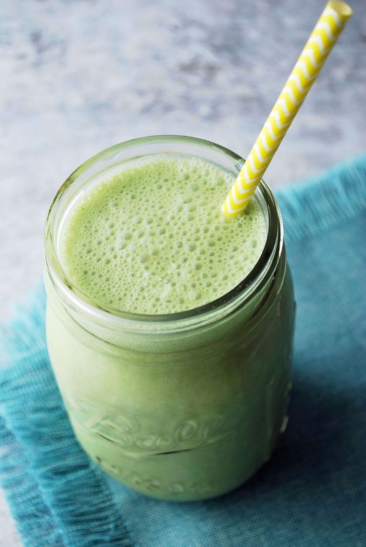 overhead shot of green oatmeal smoothie with yellow straw and blue napkin