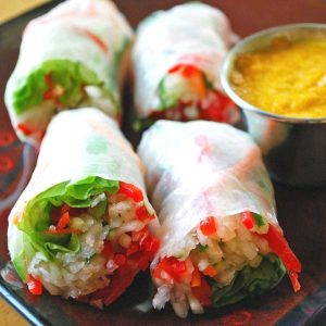 close up photo of two Vietnamese salad rolls on a plate with dipping sauce on the side