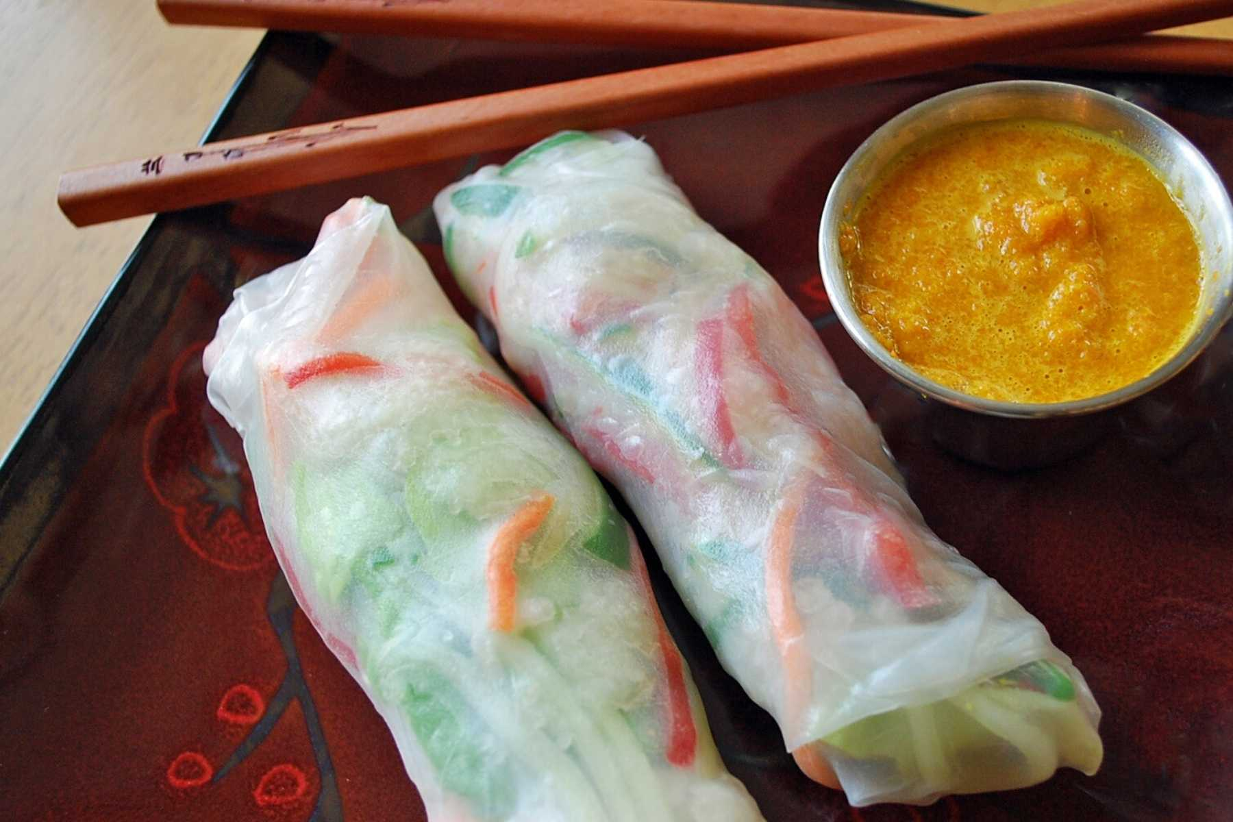 two salad rolls on a plate with ginger sauce and chopsticks