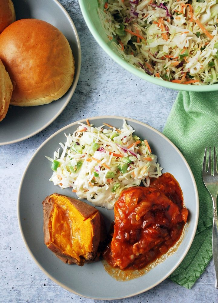 overhead photo of plate of bbq chicken with slaw and sweet potato with buns and bowl of slaw in background