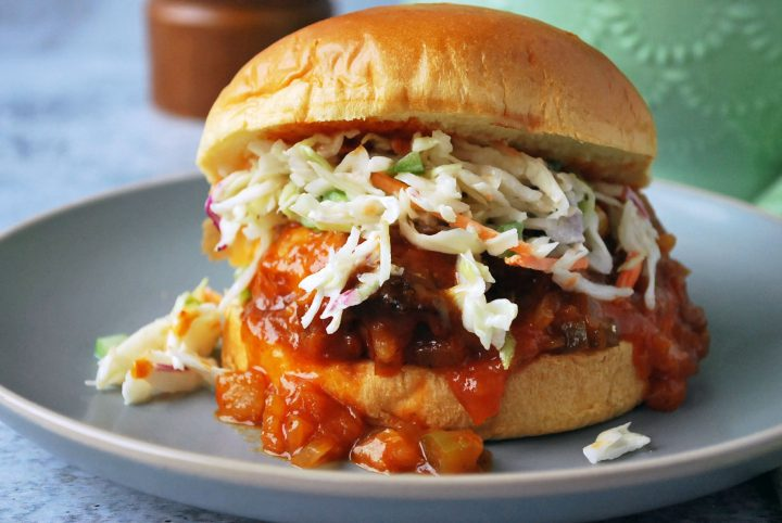 Crockpot BBQ chicken sandwich with slaw and sauce dripping out the side