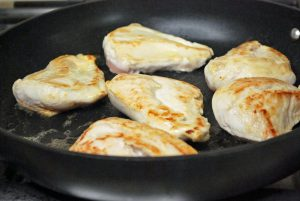 chicken breasts browning in pan