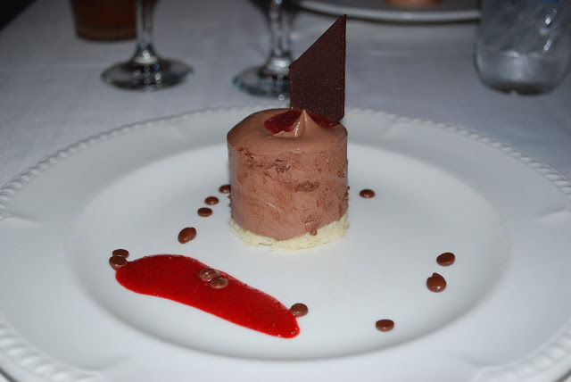 A piece of chocolate mousse on a plate with fancy drizzle