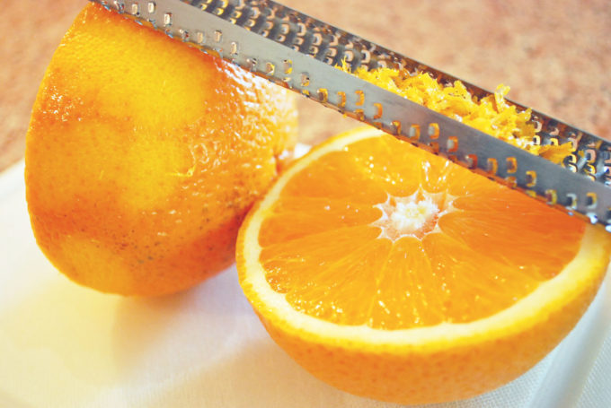 orange cut in half and a microplane grater with orange zest