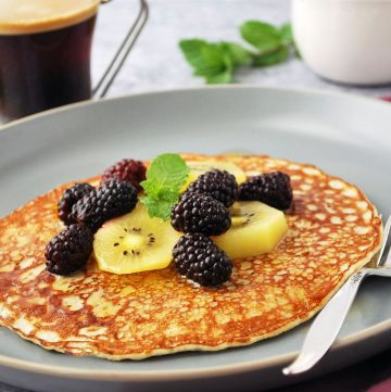 side view of banana pancake on a plate with kiwi and blackberries