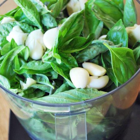 basil and garlic in a food processor bowl