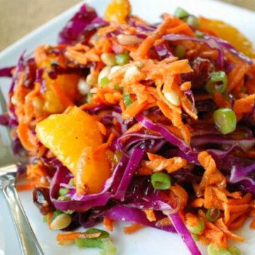shredded purple cabbage salad with green onions and mandarian oranges on a plate