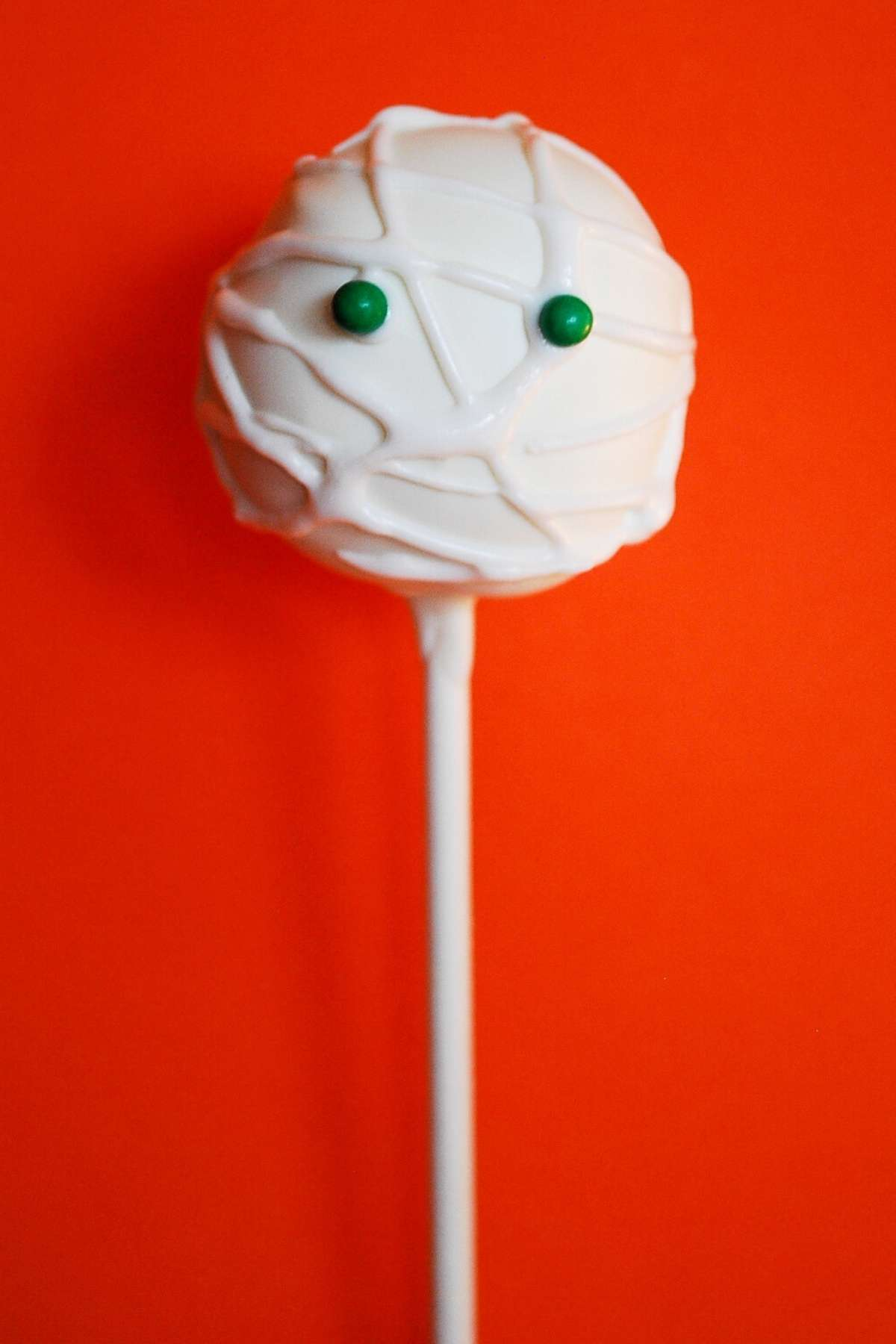 a mummy cake pop with green candy eyes