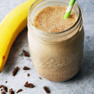 chocolate protein shake in a mason jar with green striped straw
