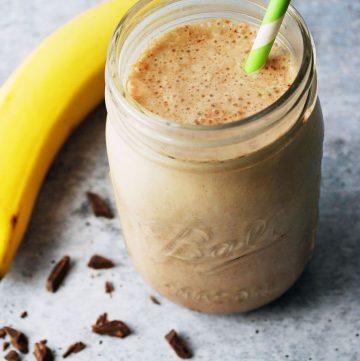 chocolate protein shake in a mason jar with green striped straw